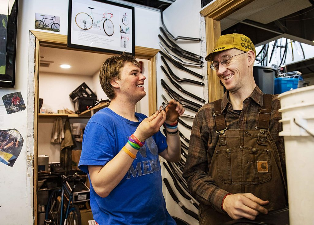 Dylan, left, and Aaron Taylor share a joke while working in the Way of Compassion bicycle project shop in Carbondale on Thursday, Feb. 13, 2020. Taylor is the director of the bicycle project and was assisting Dylan in a project. Dylan is a part of the Ascendigo nonprofit organization that assists and aims to empower people with Autism Spectrum Disorder. (Kelsey Brunner/The Aspen Times)