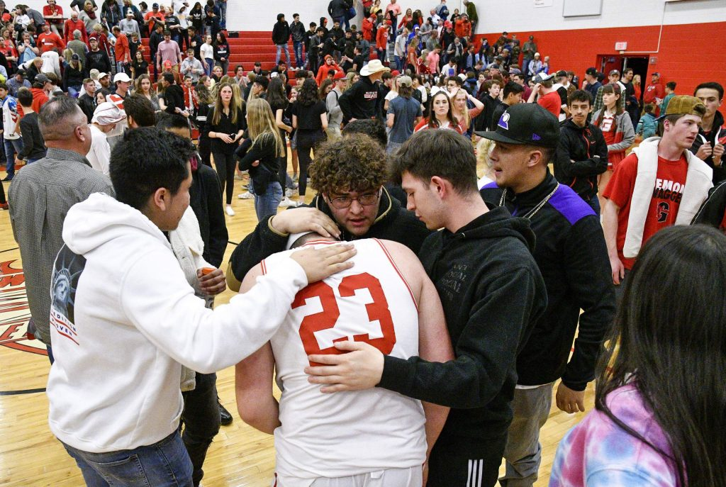 Glenwood's John Iuele is consoled by his friends and classmates after the Demons' season came to an end Saturday at home against Pueblo West in the 4A playoffs..