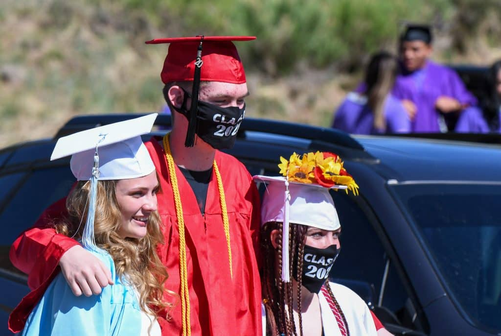 A trio of Yampah Mountain High School 2020 graduates stand for a photo before the start of the drive-in graduation ceremony Friday morning.