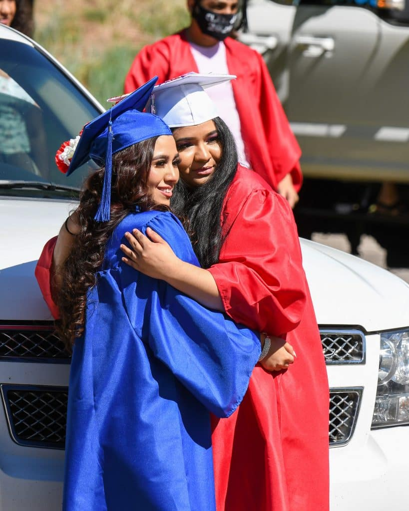 A pair of Yampah Mountain High School 2020 graduates stand for a photo before the start of the drive-in graduation ceremony Friday morning.