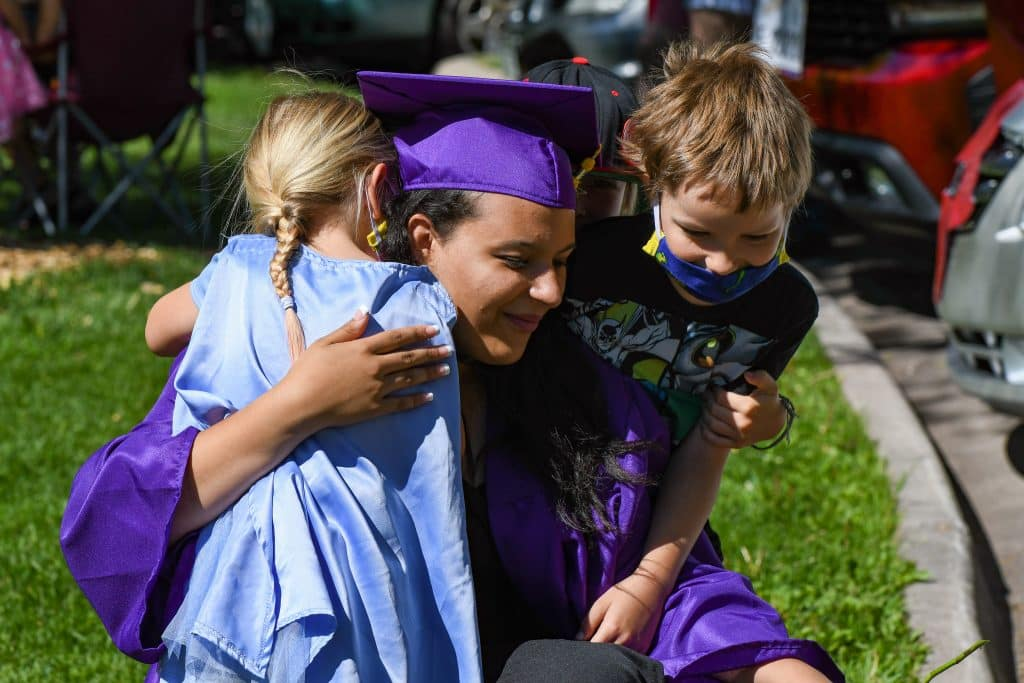 A Yampah Mountain High School class of 2020 graduate is embraced by family before the start of the drive-in ceremony on Friday morning.