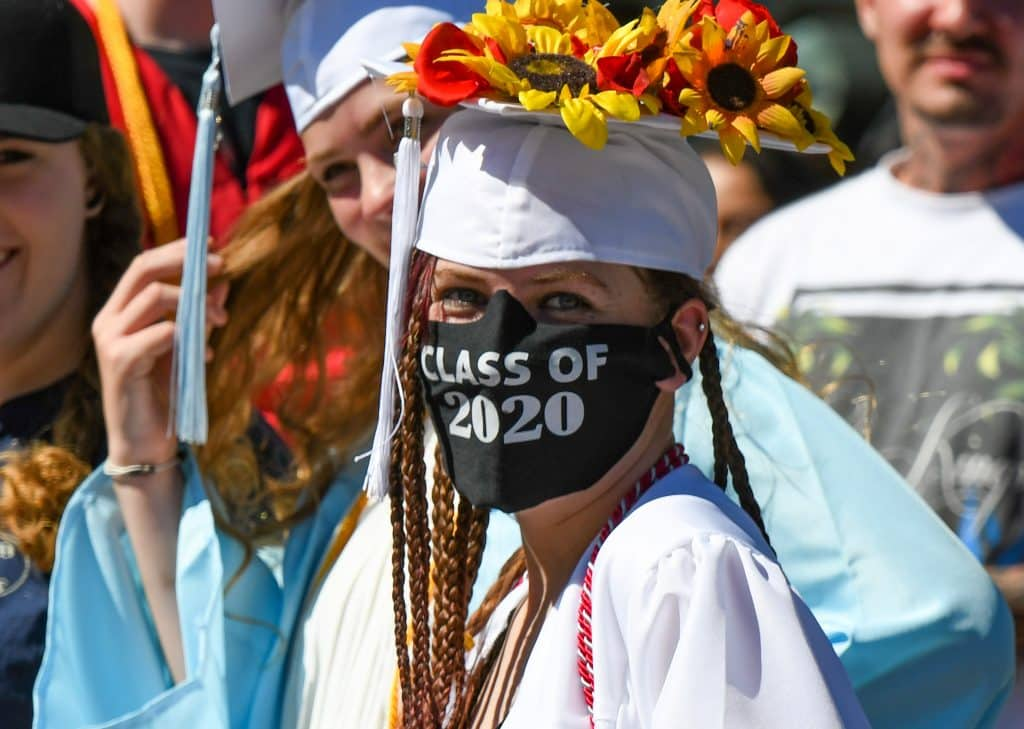 A Yampah Mountain High School class of 2020 graduate hangs out with friends before the start of the drive-in graduation ceremony on Friday morning.