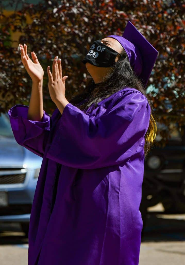 A Yampah Mountain High School graduate laughs during a speech by her advisor before recieving her diploma at the drive-in graduation ceremony on Friday morning.