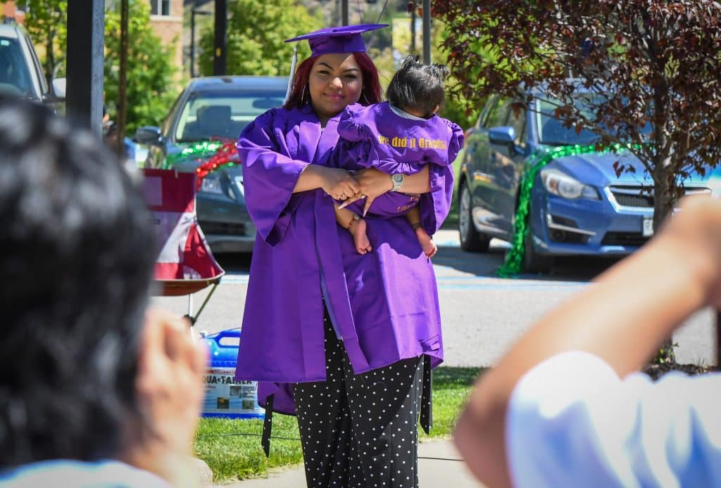 A Yampah Mountain High School graduate looks to her family before recieving her diploma at the drive-in graduation ceremony on Friday morning.