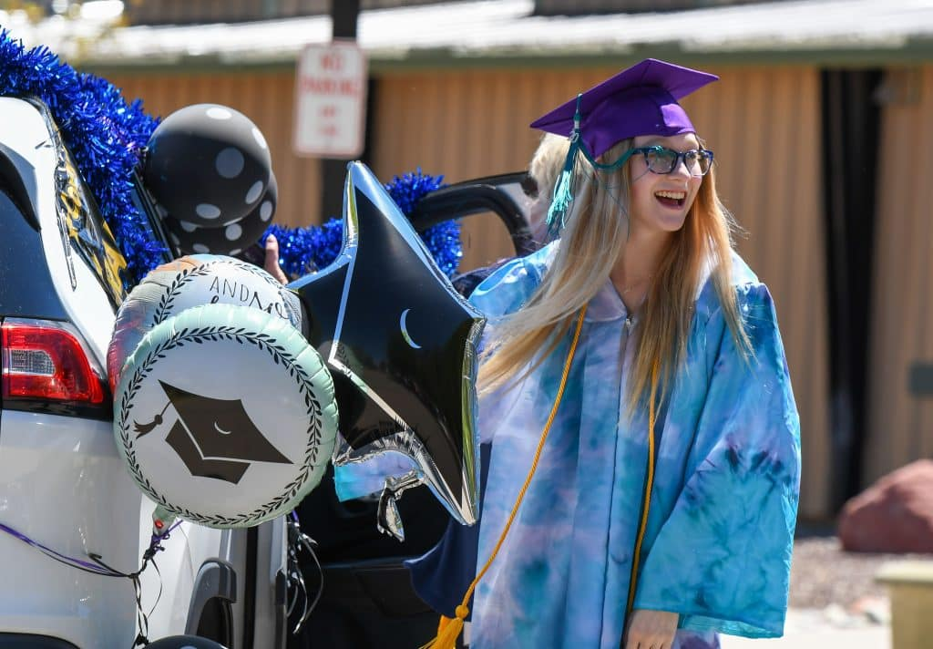 A Yampah Mountain high School graduate reacts to supporters during the drive-in graduation ceremony on Friday morning.