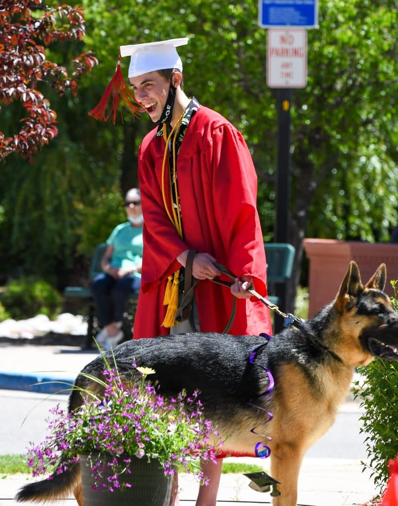 A 2020 Yampah Mountain High School graduate and his dog listen in as his advisor says a few words during the drive-in ceremony on Friday morning.