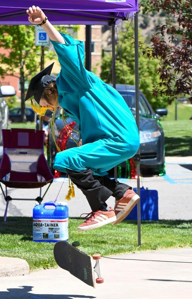 A Yampah Mountain High School graduate performs a trick on his skateboard just before receiving his diploma at the drive-in graduation ceremony on Friday morning.