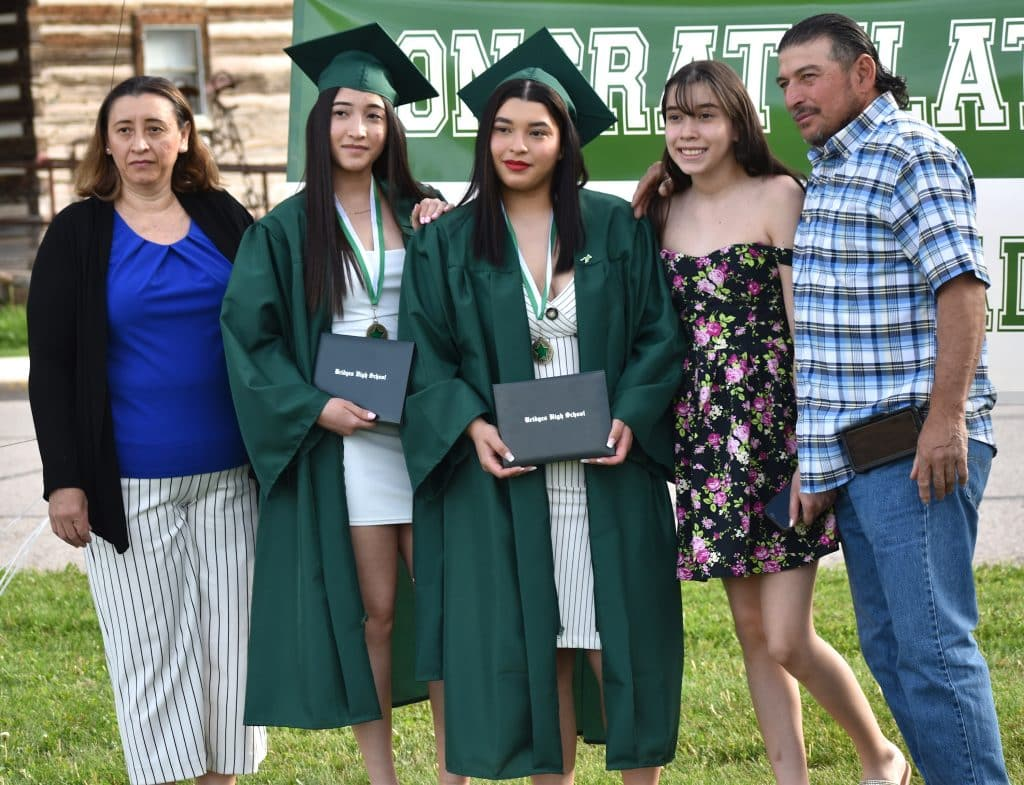 Sister graduates Fatima and Margarita Bonilla pose for a family photo following the Bridges High School ceremony Friday evening in Carbondale.
