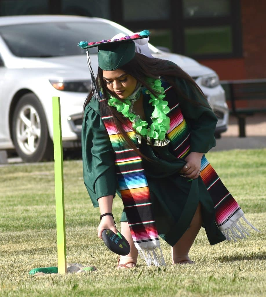 Bridges High School graduate Janneth Hernandez places a rock in the center of the ring of graduates to mark her passage, during the school's Friday evening ceremony in Carbondale.