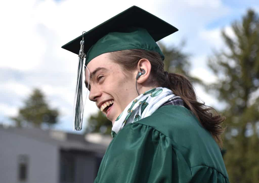 Bridges High School graduate Rudy Phelps reacts as a fellow graduate is recognized during the school's drive-in graduation ceremony in Carbondale Friday evening.