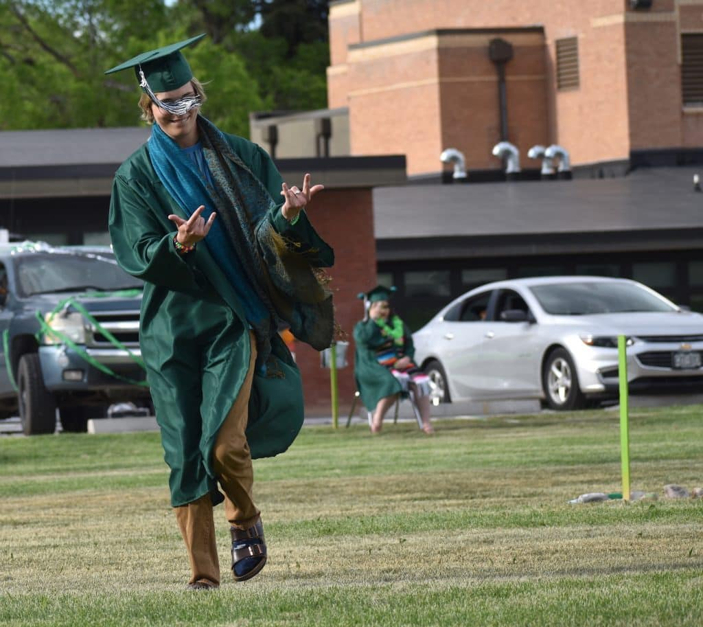 Bridges High School graduate Ryder Itzler reacts after placing his rock in the center of the circle during the school's graduation ceremony Friday evening in Carbondale.