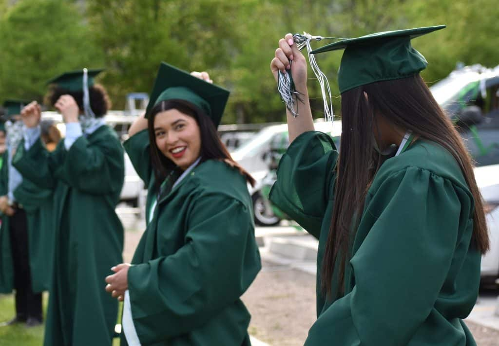 Sisters and now Bridges High School graduates Margarita and Fatima Bonilla turn their tassels during the school's graduation ceremony Friday evening in Carbondale.