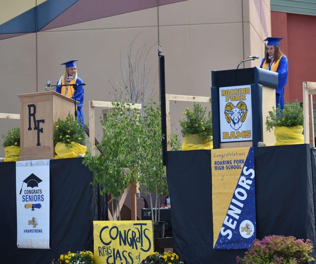 Roaring Fork High School class of 2020 co-valedictorian Lucia Penzel, left, and senior head girl Isabella Lee give their address during the drive-in graduation in Carbondale Saturday morning.