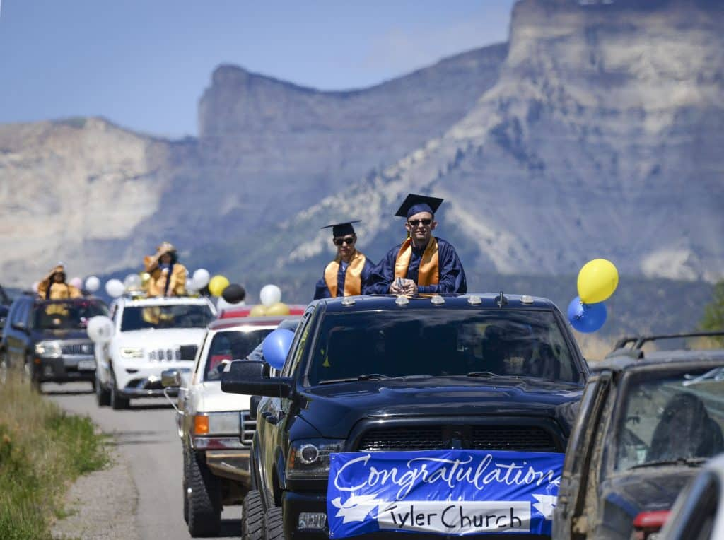 Flanked by Anvil Points and the Roan Plateau Rifle High School Class of 2020 begins their processional down W Sixteenth Street as they loop through town last Saturday. (Kyle Mills / Citizen Telegram)