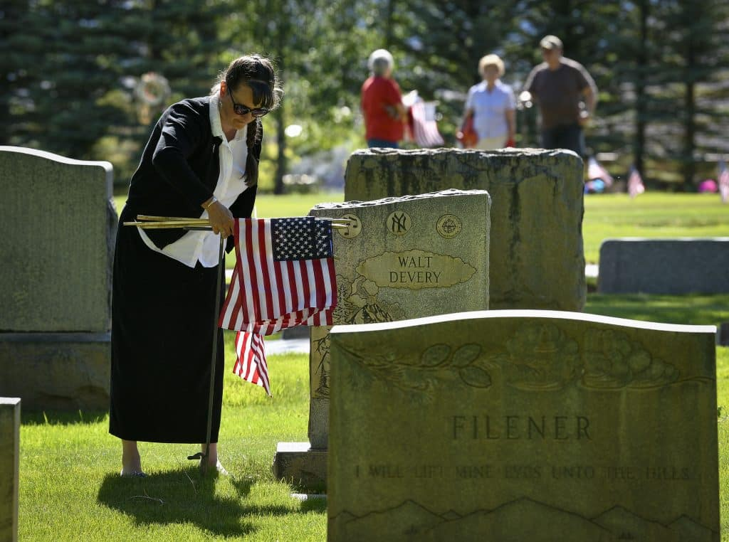 Misty Williams of Rifle volunteers her time to plant flags near the gravestones of veterans buried at Rose Hill Cemetery in Rifle. (Kyle Mills / Citizen Telegram)