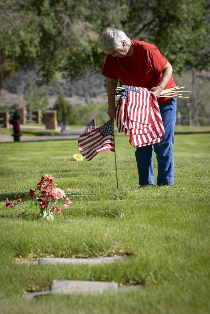 Connie Hollenbeck of Rifle places a flag to honor a veteran buried at Rose Hill Cemetery last Thursday. Hollenbeck, the president of the American Legion Auxiliary has volunteered to honor the soliders from over a decade.