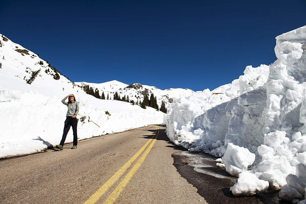 Independence Pass Foundation executive director Karin Teague walks down the road in between towering snow walls after CDOT cleared that section of road on Tuesday, May 5, 2020. (Kelsey Brunner/The Aspen Times)
