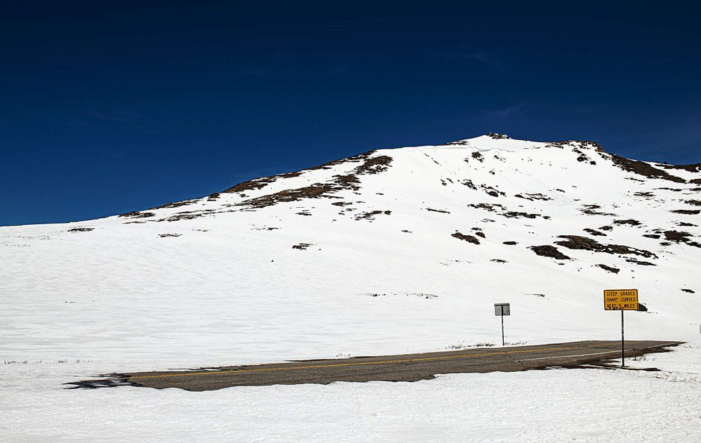 A melted part of the road at the Independence Pass summit peeks out from the snow on Tuesday, May 5, 2020. (Kelsey Brunner/The Aspen Times)