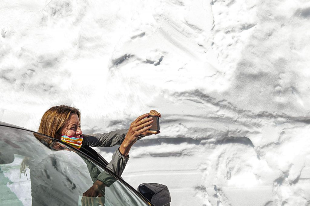 Independence Pass Foundation executive director Karin Teague takes a photograph of the high snow walls surrounding the road on Tuesday, May 5, 2020. (Kelsey Brunner/The Aspen Times)