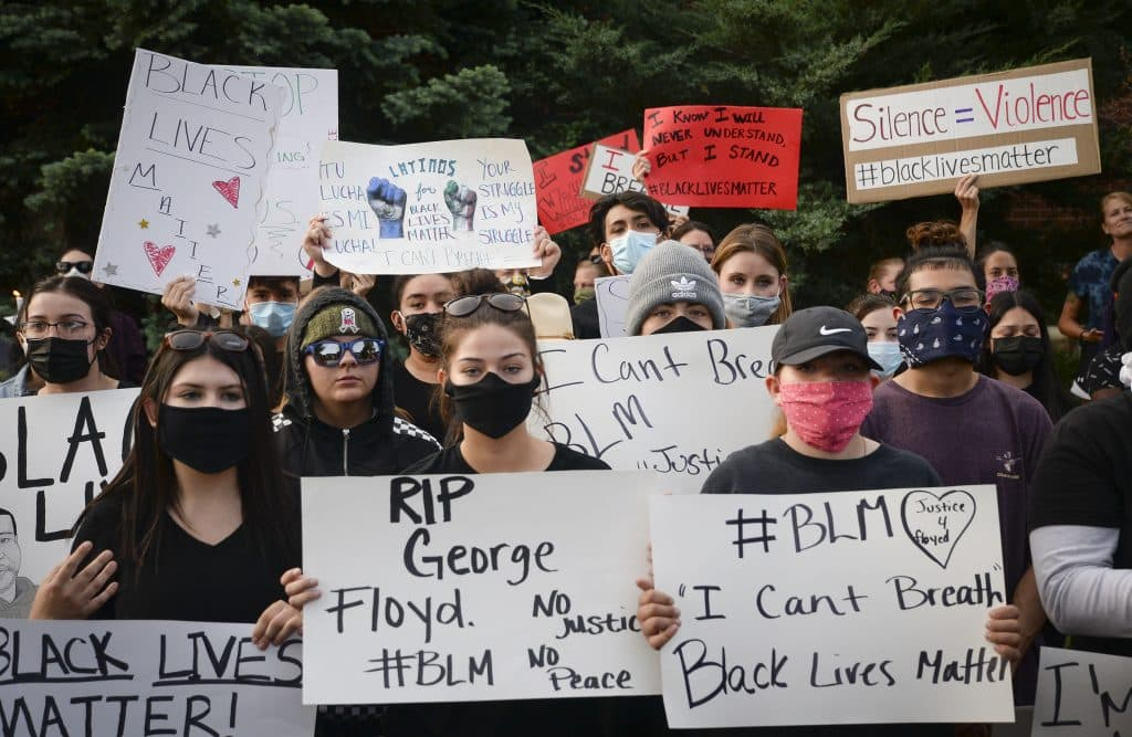 Standing silent residents hold signs of support for Black Lives Matter.