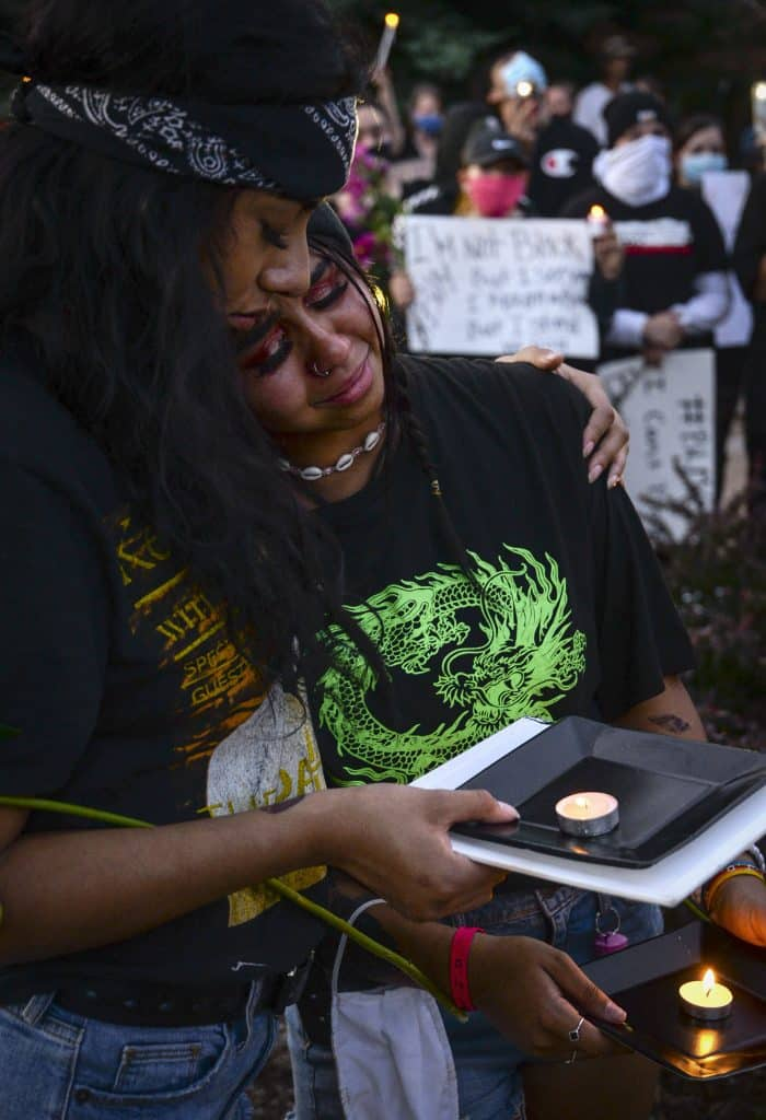 Guilari Ruiz of Rifle comforts Zyanni Vandoren of New Castle as they observe a moment of silence during Tuesday nights vigil in front of city hall in Rifle.