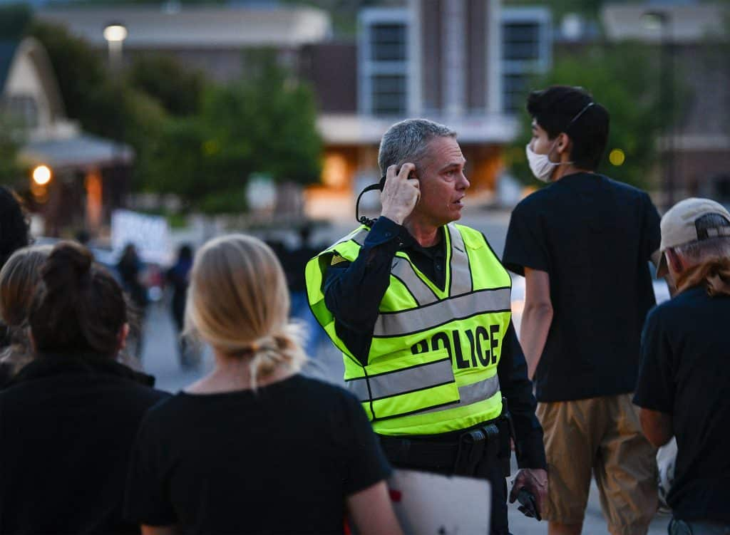 Rifle Police Chief Tommy Klein directs traffic as residents cross Railroad Avenue after Tuesday's vigil downtown.