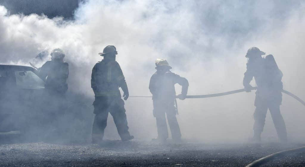 Under the watchful eye of Terry Cox, division chief from Roaring Fork Fire Rescue (second from left) CMC Rifle Fire Academy cadets navigate a heavy cloud of smoke to extinguish a car fire during last Sunday's burn day in Glenwood Springs. (Kyle Mills / Citizen Telegram)