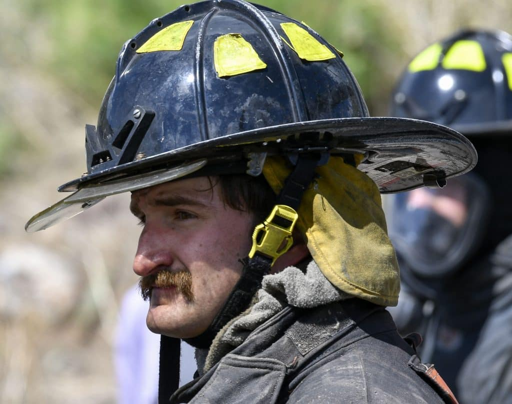 CMC Fire Academy cadet Ambrose Menard watches other cadets battle a car fire during last Sunday's burn day. Menard originally from Highlands Ranch, now lives in Rifle where he works on a ranch when he is not volunteering at CRFR.