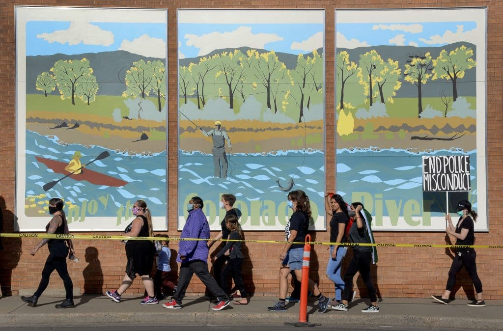 Black Lives Matter participants walk by a mural of the Colorado River Valley as they march through Rifle to mark the anniversary of Juneteenth. Hundreds of BLM supporters and pro-police supporter gathered in Rifle for the event.