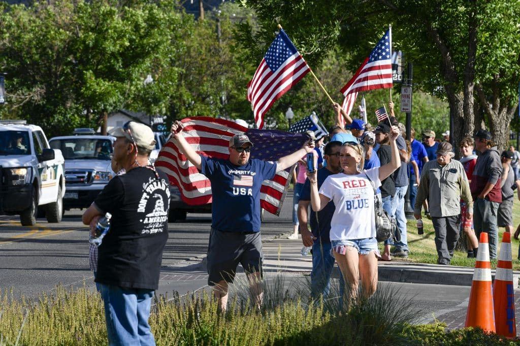 Pro-police supporter show their patriotism as they walk across from City Market on their way to the police Department last Friday.