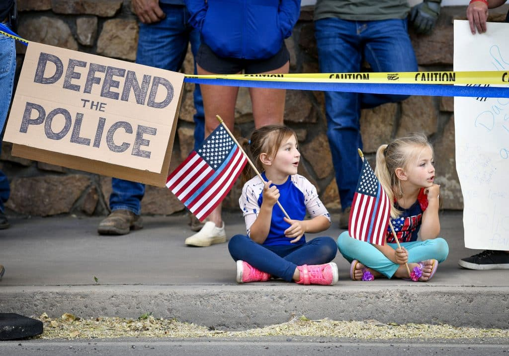 A few of the younger members of the pro-police march wait along Railroad Avenue for the march to the police department to begin last Friday in Rifle.