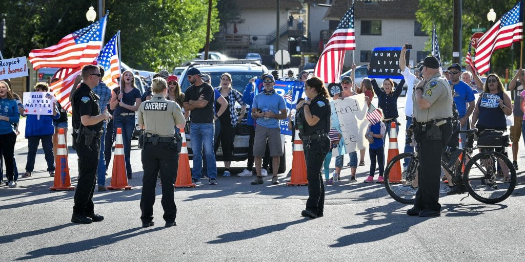 Law enforcement officers with Carbondale Police Department and Garfield County Sheriff's Office help keep distance between both sides participating in last Friday's march through Rifle.