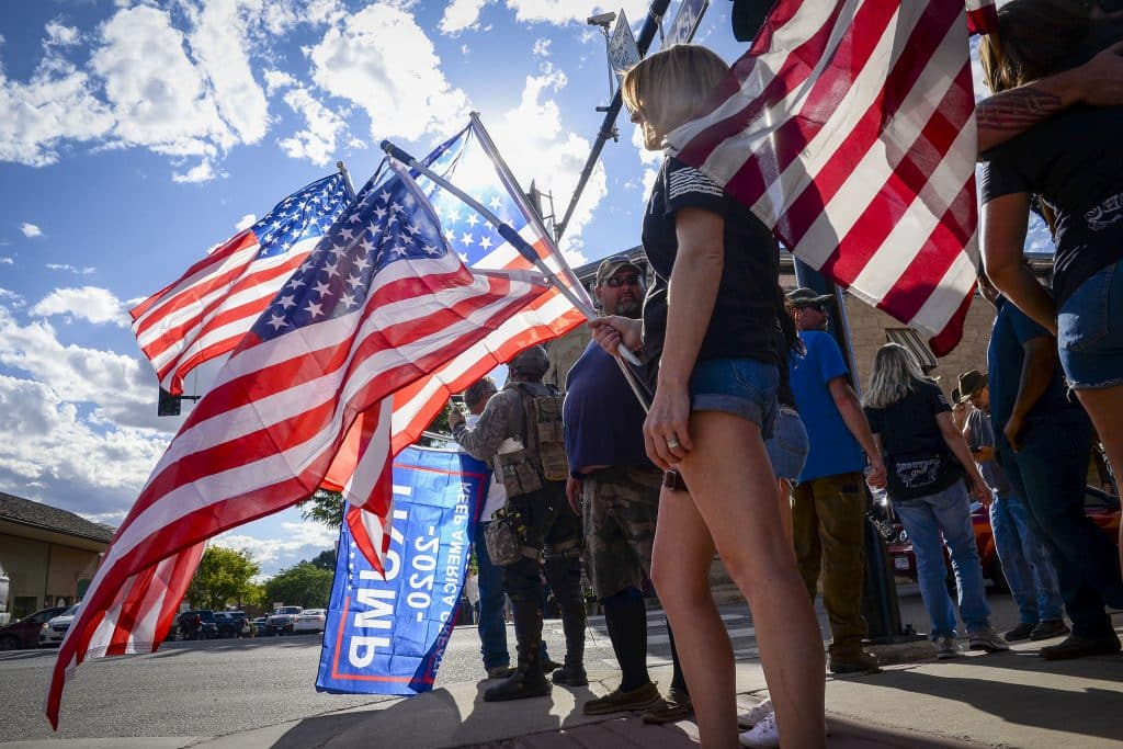 Participants in the pro-police gathering hold american flags as thye wait for the march through Rifle.