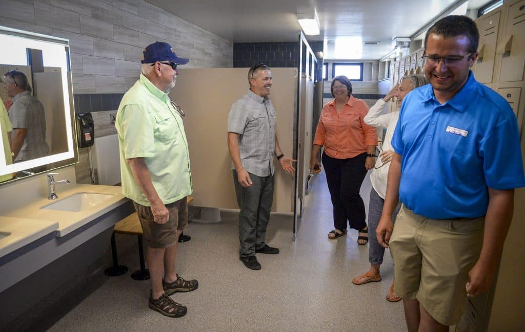 Members of the Rifle city council including, Councilors Joe Carpenter, and Sean Strode, Mayor Pro Tem Theresa Hamilton, and Mayor Barb Clifton take a tour through the new locker rooms with Austin Rickstrew, recreation coordinator of aquatics.