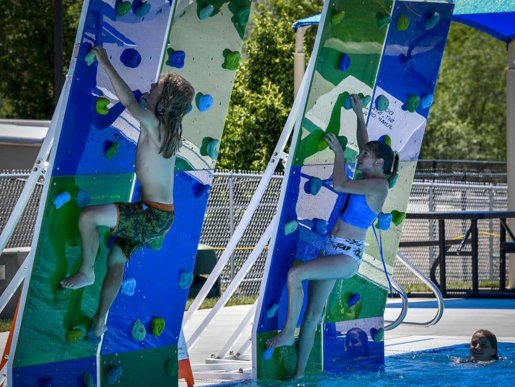 Swimmers climb up the climbing walls before plunging back into the new six-lane lap pool Sunday.