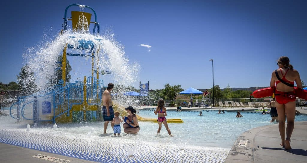Families enjoy the zero-depth entry pool during Sunday's soft opening at Rifle Metro Pool.