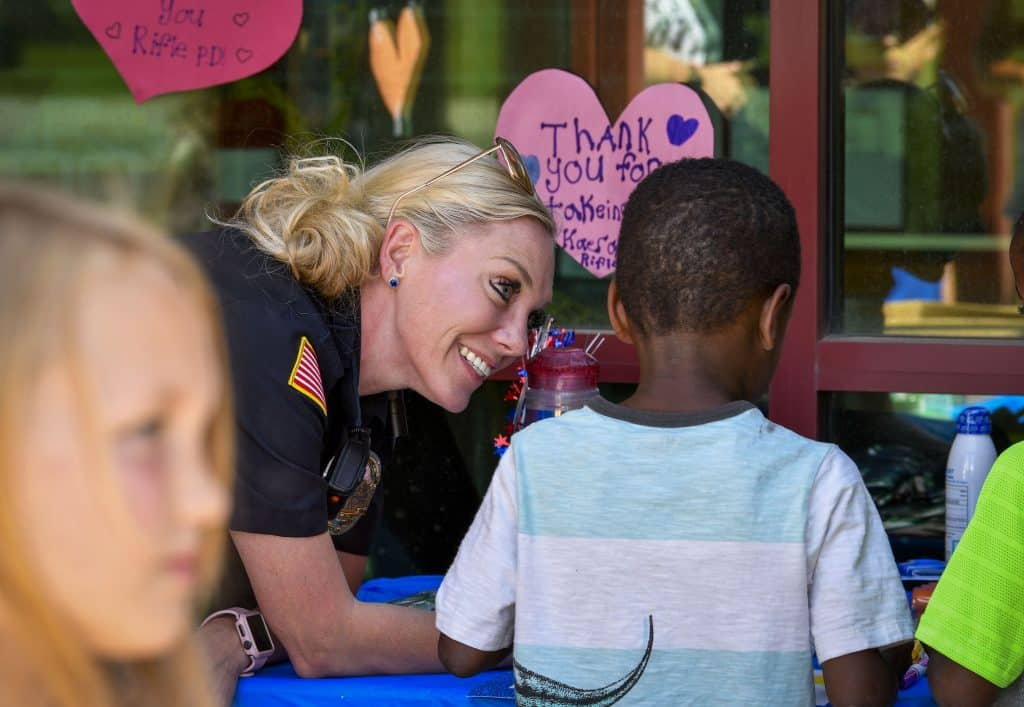 Rifle Police Officer Kelli Litzau talks with a few of the children as they write messages for local law enforcement officers during the event last week.