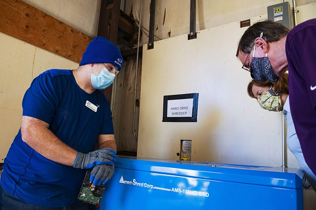 Blue Star Recyclers' Danny Hennessy, left, Ann Harris, center, and Ken Robinson watch as a hard drive is shredded during the grand opening of the Basalt location on Wednesday, June 24, 2020. (Kelsey Brunner/The Aspen Times)