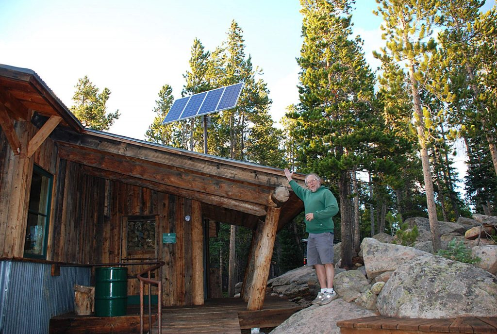 Scott Ely stands outside of the Fritz Hut on Smuggler Mountain. Sunsense constructed the solar electric system to the hut built in 1997.