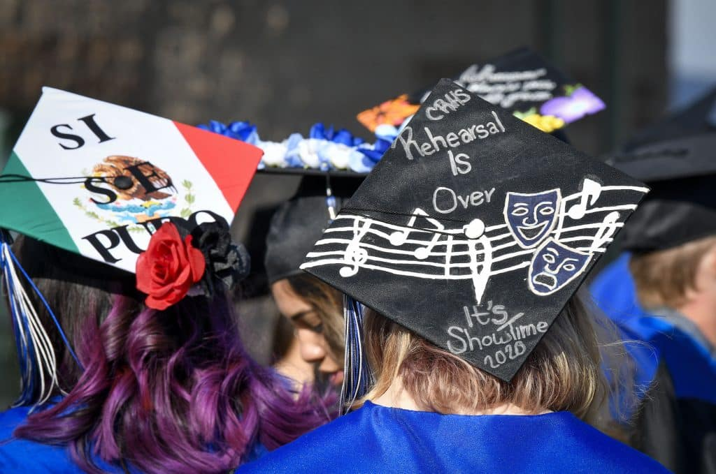 With decorated caps soon to be graduates of Coal Ridge High School wait to walk across the stage during Sunday's in-person graduation in New Castle.