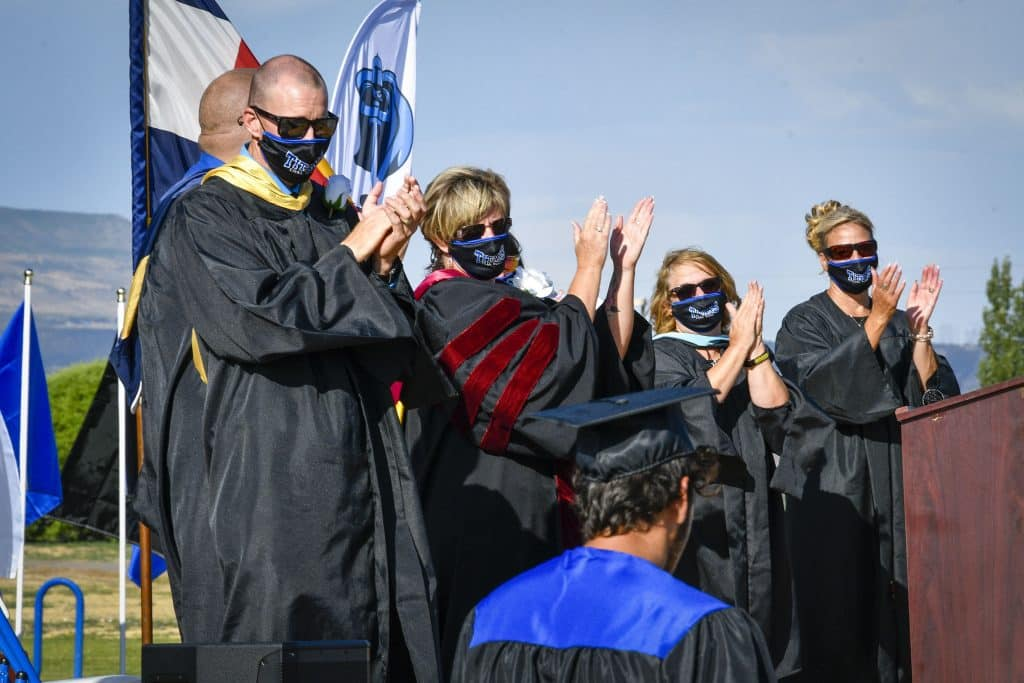 Coal Ridge High School staff and Garfield Re-2 staff applaud as students walk across the stage Sunday during day 2 of commencement ceremonies in New Castle.