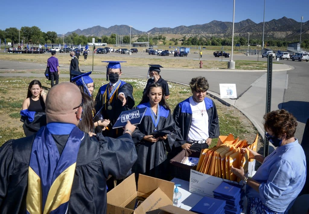 Coal Ridge High School staff hands out yearbooks and diplomas after Saturday's in-person graduation in New Castle.