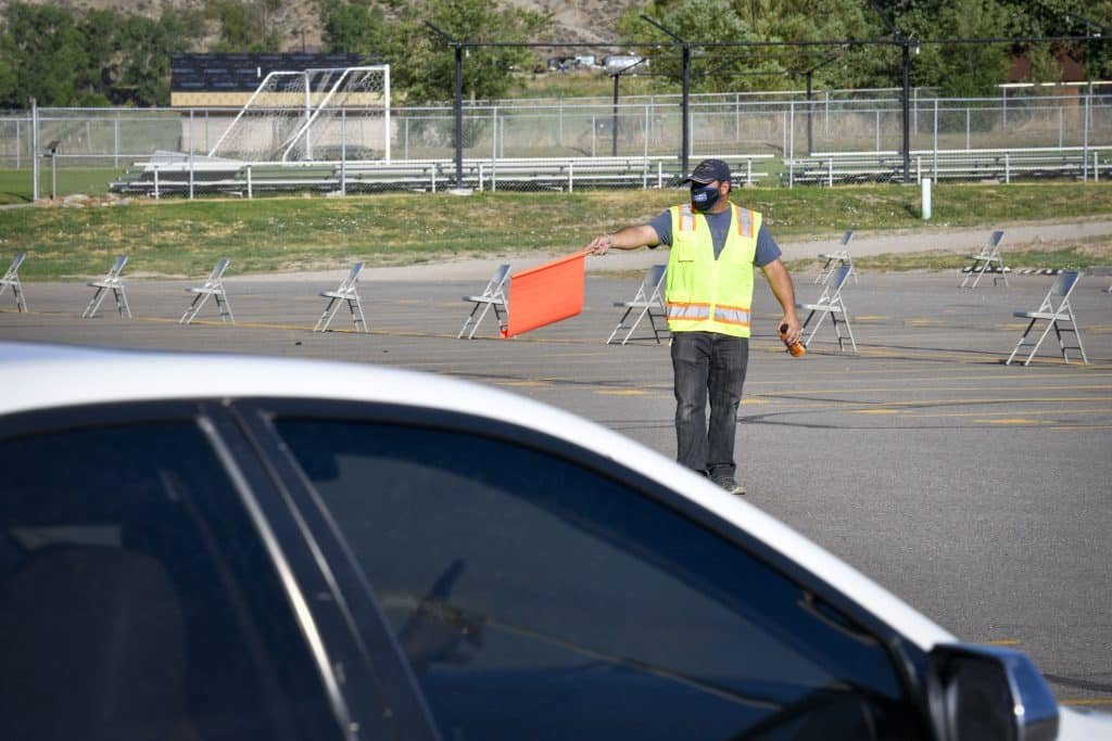 Garfield School District Re-2 staff directs traffic into the parking lot as they prepare for day 1 on the Coal Ridge High School in-person graduation ceremonies last Saturday in New Castle.