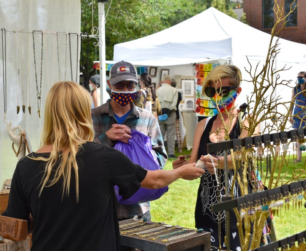 Customers check out one of the vendor booths at the downtown Makers Market.
