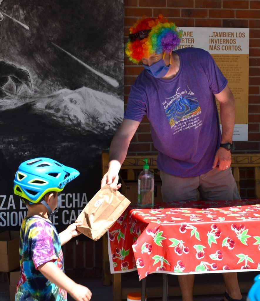 Carbondale Mayor Dan Richardson hands out a prize packet to a young participant in the Mountain Fair family scavenger hunt Sunday afternoon.