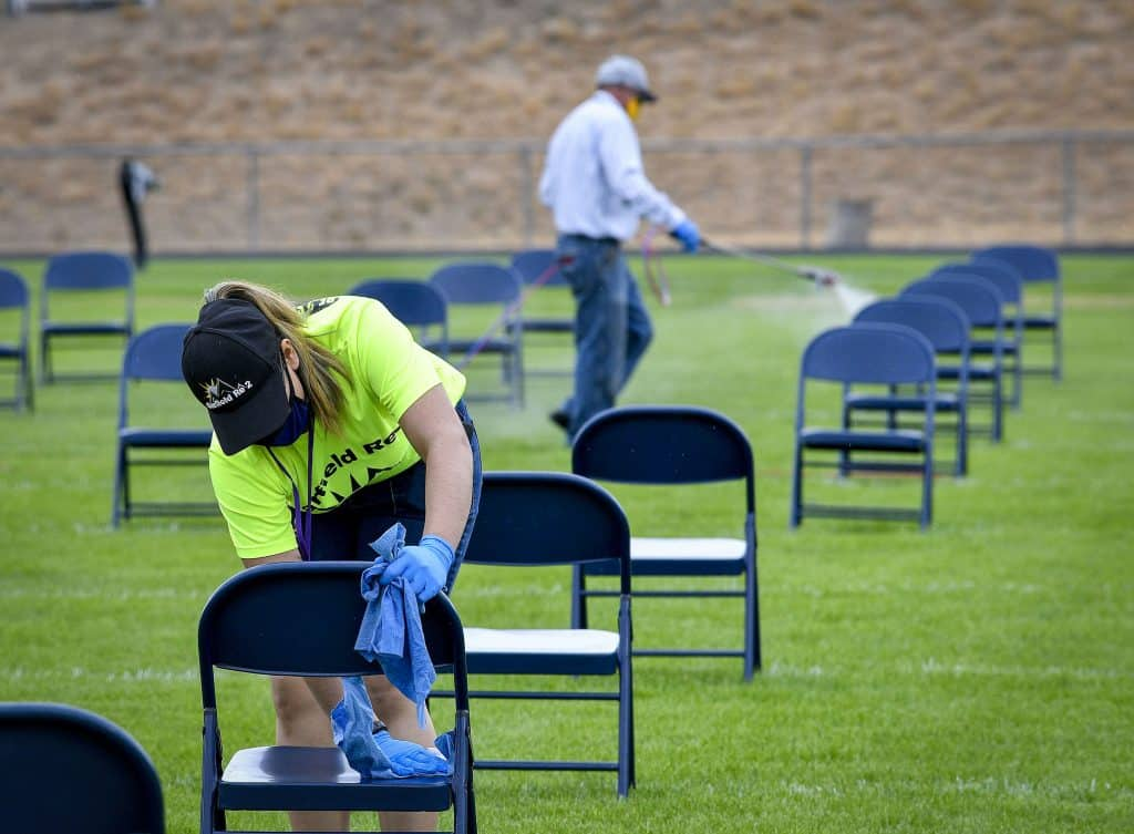 Garfield School District Re-2 staff disinfects and clean the seats for graduates after the first of three ceremonies at Bear Stadium Saturday in Rifle.