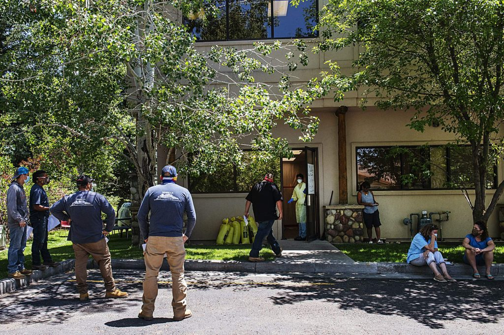Employees of Binbilla Landscaping line up outside of the MidValley Family Practice sick entrance to get tested for COVID-19 in Basalt on Thursday, July 2, 2020. The landscaping company tested fifteen of their employees as precaution after one of their employees tested positive 12 days prior. (Kelsey Brunner/The Aspen Times)