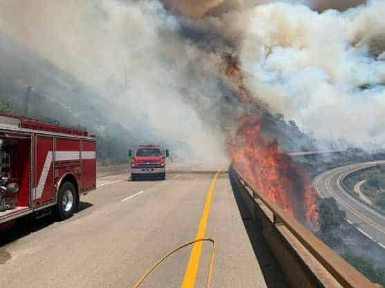 Flames from the Grizzly Creek Fire lick over the westbound lanes of Interstate 70.