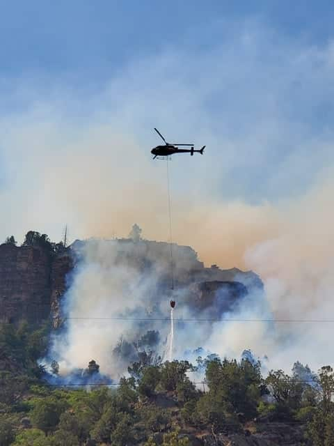 A helicopter makes a water drop on the Grizzly Creek Fire Monday afternoon.