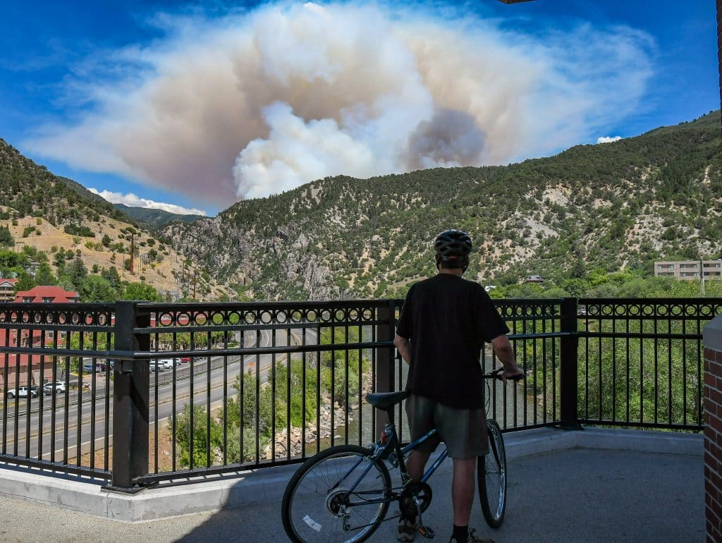 A man watches from the Grand Avenue Pedestrian Bridge as smoke billows from the Grizzly Creek Fire in Glenwood Canyon on Monday afternoon.